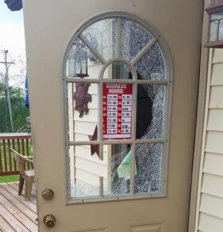 Así quedó la puerta del local tras el robo.