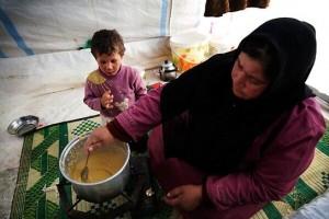 Saleha Mustafá, calentando una sopa de lentejas dentro de su tienda en el campo de desplazados (© Anna Surinyach).