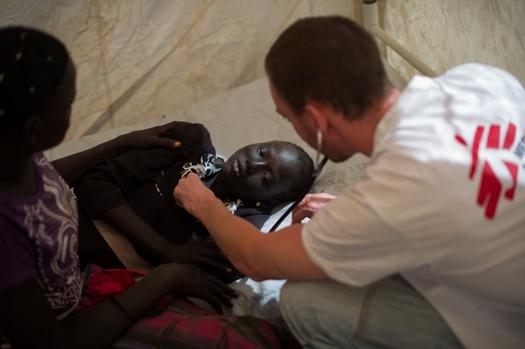 Un médico de MSF atiende a una mujer en la clínica que Médicos Sin Fronteras en el campamento de desplazados instalado en la Misión de la ONU para Sudán del Sur (UNMISS) en Juba. © Phil Moore