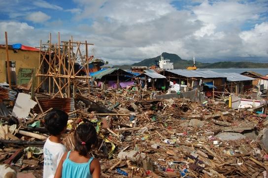 Dos niños observan la destrucción causada por el tifón en uno de los suburbios de Tacloban. © Sophie-Jane Madden/MSF