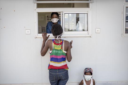 Una madre junto a su hijo en el mostrador del dispensario de la zona industrial de Matsapha, Suazilandia. ©Sven Torfinn.