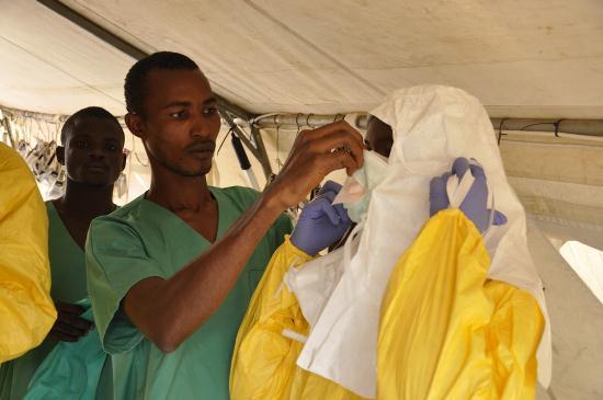 Miembros de MSF aseguran el traje de protección antes de entrar en el centro de tratamiento  del Ébola Copyright: Amandine Colin/MSF