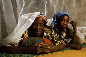 Latifatou (10) con su abuela Zarata (aproximadamente 70) debajo de un mosquitero  en la región de  Sanmatenga en  Burkina, Faso el 25 de Febrero de 2014