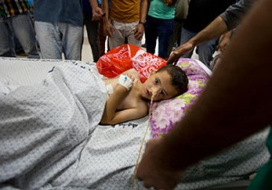 Kinan, de 5 años, fue herido durante un ataque aéreo israelí. Aquí está rodeado por familiares y personal médico en la Unidad de Cuidados Intensivos del hospital al-Shifa de la ciudad de Gaza, en el sur de la Franja de Gaza.  © UNICEF/NYHQ2014-0901/El Baba