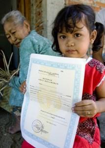 Pequeña niña enseña su certificado de nacimiento