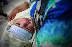 Un familiar se ocupa de Ayla mientras su madre recibe los cuidados post-parto. Copyright: Gabrielle Klein/MSF