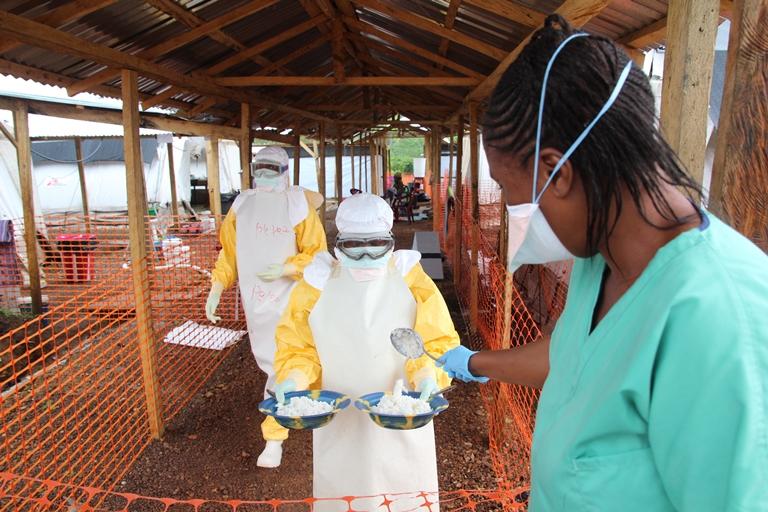 Distribución de alimentos a los pacientes confirmados de Ébola en la zona de alto riesgo. No existe contacto entre el personal que viste los trajes de protección en zona alta de riesgo y la zona de bajo riesgo. Una nutrición de calidad es importante para mejorar el sistema inmunológico del paciente y ayudarle a combatir el virus.