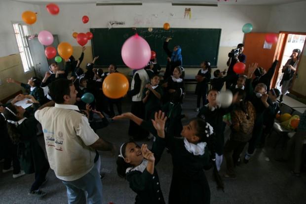 Un asesor dirige un juego con globos en un aula Gaza, parte de un esfuerzo para reincorporar poco a poco a los niños en el aprendizaje a través de actividades recreativas.