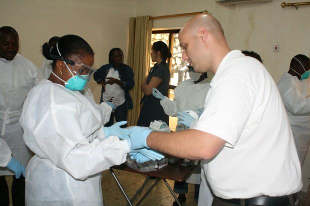 El instructor del Centro de Control y Prevención de Enfermedades de Atlanta, Ben Levy, enseña a una alumna a utilizar los dobles guantes de látex para evitar el contagio de ébola. En Sierra Leona, ha habido más de 80 fallecidos a causa del ébola, y al menos 100 se han contagiado. (©UNICEF/2014/Bade)