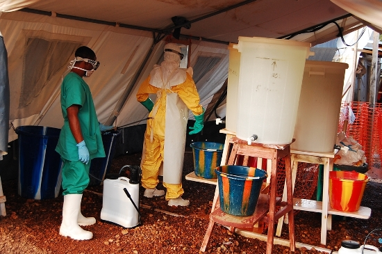 Un higienista guía el proceso de desvertirse y rocía con una solución de cloro cada uno de los elementos del traje de protección. Fotografía: Fathema Murtaza/MSF