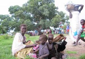 Cuaca, de 22 años, con sus hijas Nyadieng, Mawiek y Nyawech, a la espera de recibir vales de comida durante una Misión de Respuesta Rápida de UNICEF y el PMA en Pathai, en el estado de Jonglei, Sudán del Sur. Ya lleva varias horas esperando para registrarse. (© UNICEF South Sudan/2014/Donovan)