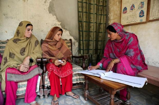 Shagufta toma notas mientras conversa con mujeres embarazadas para llevar un registro de sus revisiones periódicas. Usa una parte de su casa como centro de atención a la maternidad.