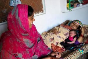 Shagufta Shahzadi se sienta al lado de una madre que descansa tras dar a luz a su bebé