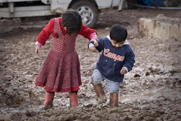 Dos niños cruzan las calles llenas de barro del campo de desplazados internos Bab Al Salame  de Aleppo. (© UNICEF/NYHQ2014-0015/Diffidenti)