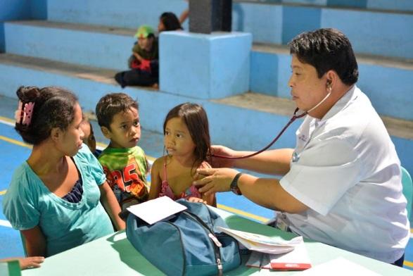 El doctor Paulina hace a Elna y a sus hijos un chequeo médico en el centro de evacuación © UNICEF Filipinas / 2014 / Andy Brown