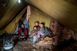Hakim se acurruca con su madre y su hermana menor en su tienda de campaña en el campamento de Domiz, en Irak.