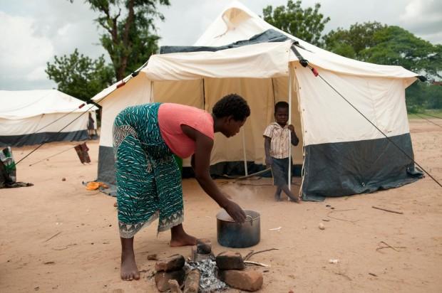 Martha Watson prepara una comida para ella y para su hijo que la observa desde su carpa del refugio, un campamento para personas afectadas por las inundaciones, en la escuela Bangula FP del distrito meridional de Nsanje. ©UNICEF/NYHQ2015-0097/van de Merwe