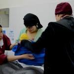 Farzana y su bebé son envueltas en una gran tela de color azul. El contacto piel con piel con la madre calienta al recién nacido, pero sobre todo crea vínculos psicológicos entre el bebé y la madre. Fotografía de Mathilde Vu/MSF