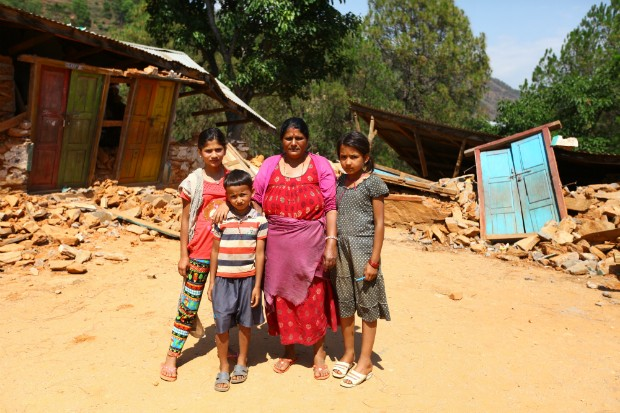 , Rita Pyakhurel, 56, principal of Shree Kalika Secondary School in Gerkhutar Village Development Committee in Nuwakot, stands in front of the destroyed school with her students Shanti Pyakhurel, 13, Sanjog Chalise, 8, and Samikshya Chalise, 12. Rita is worried about how to rebuild it, as her students are constantly asking her when they can return to their classes. Nuwakot is one of the 12 districts in Nepal highly affected by the 25 April earthquake. Photo by Kiran Panday for UNICEF