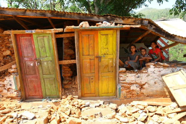 """Samikshya Chalise, 12, Sanjog Chalise, 8, and Shanti Pyakurel, 13, play inside a destroyed classroom in Shree Kalika Secondary School in Gerkhutar Village Development Committee in Nuwakot, one of the 12 districts in Nepal highly affected by the 25 April earthquake. The students live nearby and said that they come there all the time because they miss going to the school. """"We have lost both our home and school,"""" said Sanjog. Photo by Kiran Panday for UNICEF."""