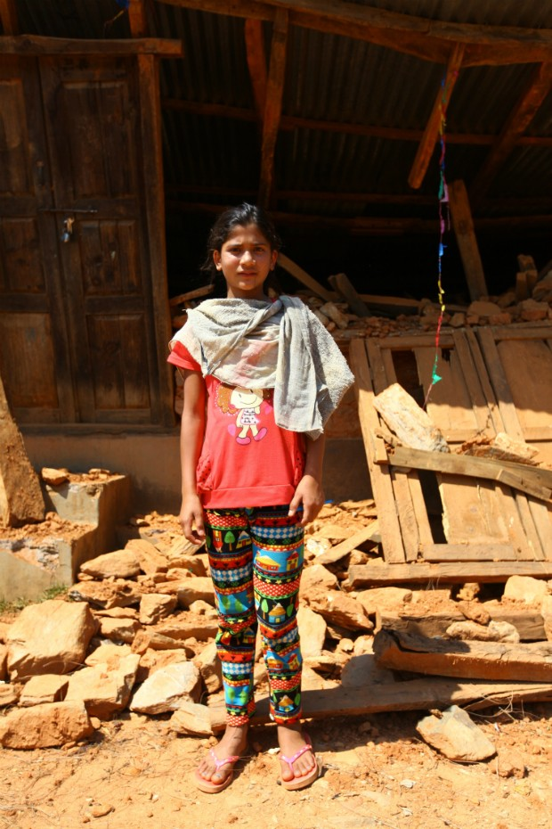 """Shanti Pyakhurel, 13, stands outside her destroyed house in Gerkhutar Village Development Committee in Nuwakot, one of the 12 highly earthquake-affected districts in Nepal. Shanti almost got killed with her four friends when they were doing homework together. Fortunately, they survived by hiding under their bed as the earth shook. Once the shaking stopped, they escaped to open space, just before the house collapsed. """"I miss doing my homework and my teachers in school,"""" she said. Photo by Kiran Panday for UNICEF"""