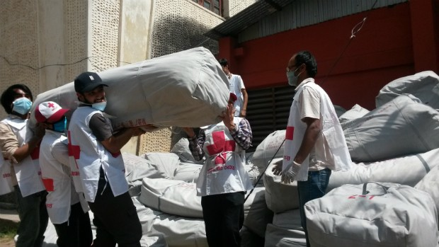 •Voluntarios y voluntarias cargando toldos plásticos para enviar a afectados por el terremoto.