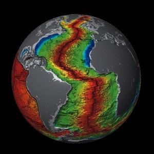 Relieve del fondo Atlántico. La cicatriz roja es la Dorsal Atlántica, una franja donde la corteza terrestre se crea separando progresivamente las costas de América de las de África y Europa. Imagen de NOAA / Rapture 2018 / Wikipedia.