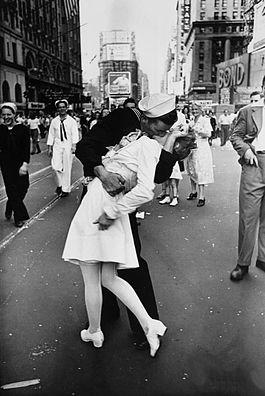 """V-J Day en Times Square, la famosa foto de Alfred Eisenstaedt para la revista 'Life' tomada el 14 de agosto de 1945. Al fondo a la derecha, el letrero """"BOND"""" con el reloj en la """"O"""" y la sombra sobre el edificio Loew. Imagen de Wikipedia."""