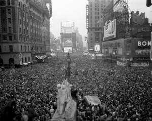 """Fotografía de Times Square tomada el 14 de agosto de 1945 a las 19:45 por el sargento de la Fuerza Aérea de EE. UU. Reginald Kenny. A la izquierda, arriba, el letrero del Hotel Astor en forma de """"L"""" invertida. A la derecha, al fondo, el edificio Loew. Imagen de Army Air Force."""