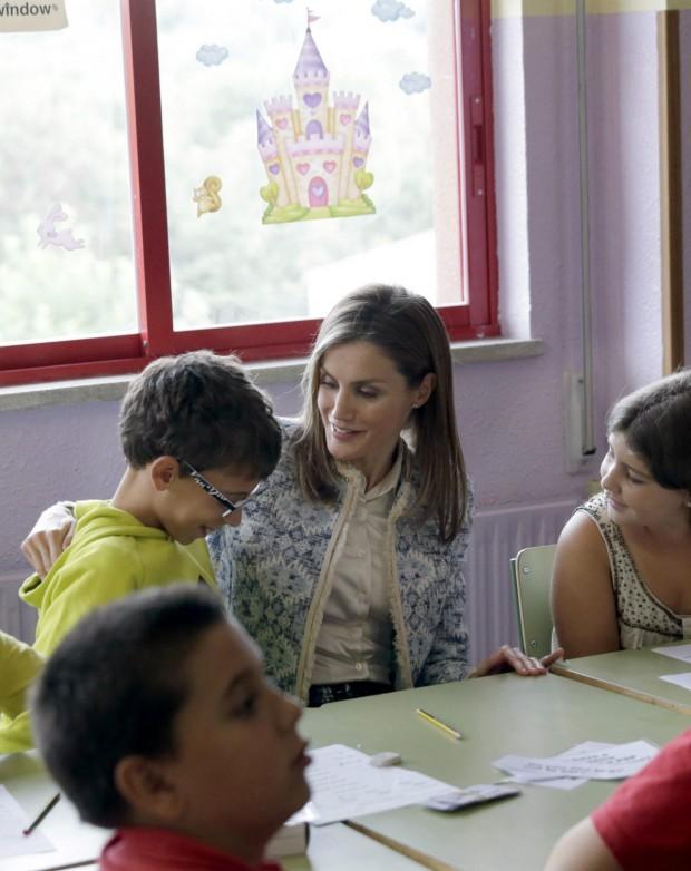 Letizia, tan perfeccionista, colocando bien la capucha a un alumno. (Lavandeira jr/ EFE)
