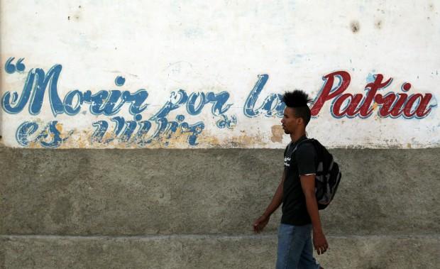 Un joven camina junto a un muro con una estrofa del himno nacional de Cuba el miércoles 15 de abril de 2015, en una calle de La Habana. (EFE)