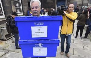 Un hombre con las urnas donde se depositan los votos del referéndum.  (Andy Rain / EFE)