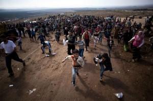 Un grupo de niños desplazados sirios corren tras un camión en un campo de refugiados. (GTRES)