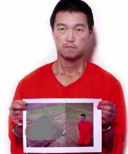 Kenji Goto sostiene una foto del segundo rehén. Fuente: Captura de Youtube.