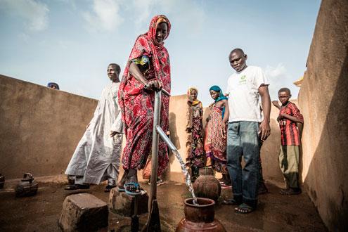 Akkoe Moussa, echando agua en un cántaro de cerámica junto a otras personas. Tiene entre 45 y 50 años y vive en Madoul, cerca de Mangalmé. En este pueblo hay dos puntos de agua limpia, y sus habitantes trabajan para mantener la higiene comunitaria.  (Foto: Pablo Tosco, cortesía de Intermón Oxfam)