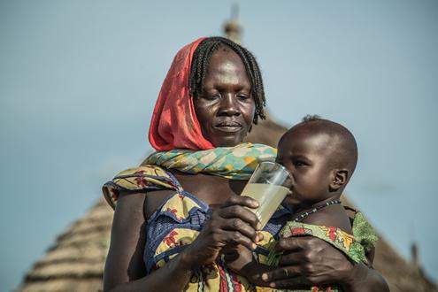 Achta Fadoul da de beber el agua del pozo a su hijo, en Midjiguir, a 23 kilómetros de Mangalmé, en el Chad. (Foto: Pablo Tosco, cortesía de Intermón Oxfam)