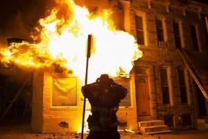 Bomberos acuden a extinguir las llamas en un edificio durante los disturbios provocados durante una protesta contra la muerte de Freddie Gray en Baltimore (Estados Unidos). (John Taggart / EFE)