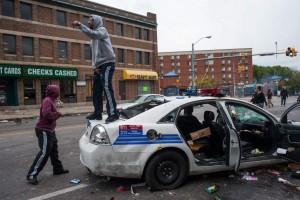 Varias personas gritan sobre un vehículo de la policía abandonado que fue atacado durante las protestastras el funeral de Freddie Gray. (EFE/NOAH SCIALOM)