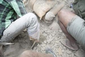 Varias personas intentan rescatar a un hombre de entre los escombros de un edificio derrumbado por el terremoto en Nepal / EFE