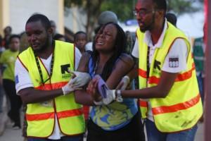 Dos sanitarios ayudan a una mujer que ha escapado de Garissa. (EFE)
