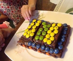 Su hermana y su prima haciéndole la tarta de cumpleaños.