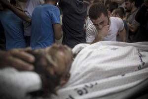 Un hombre llora próximo al cuerpo sin vida de su hermano pequeño que ha muerto en un bombardeó naval isralí en el puerto de Gaza. (EFE)