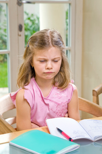 Girl doing her homework.  girl people child childhood 5-10 years interior day flat homework home work working learn learning do homework doing homework do doing book books exercise book exercise vertical one angry anger discouraged offended tired tiredness