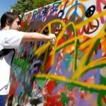 Una joven pinta un grafitti durante un acto festivo en Barcelona