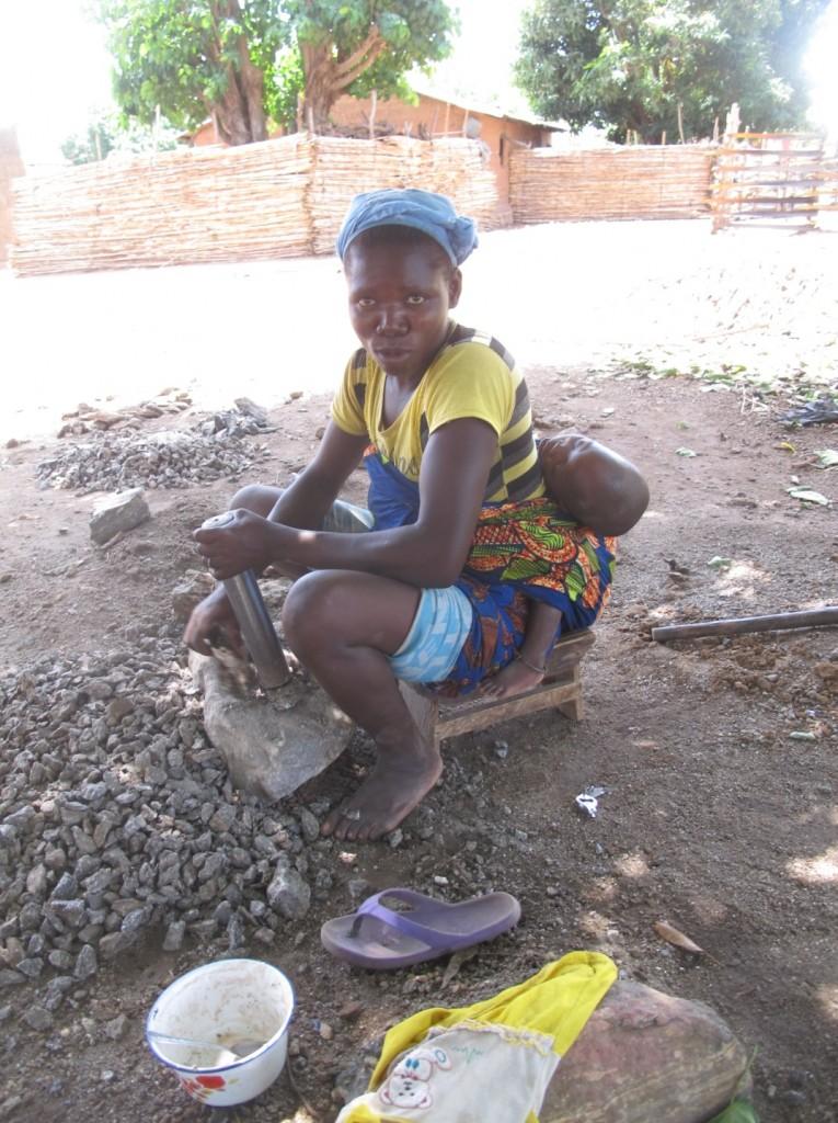 Una mujer tritura piedra de granito en una aldea de Benin (África Occidental). Imagen de Imma de Miguel