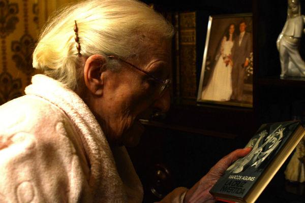 Emilia, con uno de los libros de su biblioteca. Imagen: Proyecto Vidas Mayores.