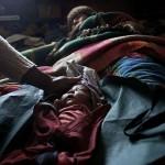 Elsa Quispe tumbada junto a su bebe de un día de edad mientras la auxiliar de enfermería Luz Maída lo tapa después de haberlo medido en Patacamaya. Fotografía de Olmo Calvo.