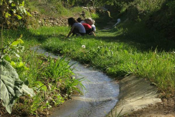Niñas y niños junto a un arroyo. Imagen de Óscar García Montes.