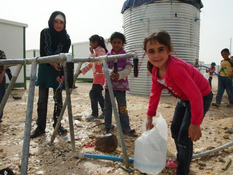 Niñas y mujeres cogen agua de las cisternas instaladas por Oxfam en el campamento de refugiados de Za'atari en Jordania. Imagen: Caroline Gluck/Oxfam