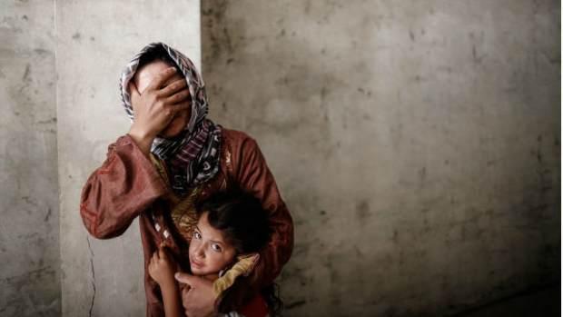 Una mujer coge a su hija mientras la aviación siria bombardea un barrio cercano a su casa. Foto: Sam Tarling / Oxfam